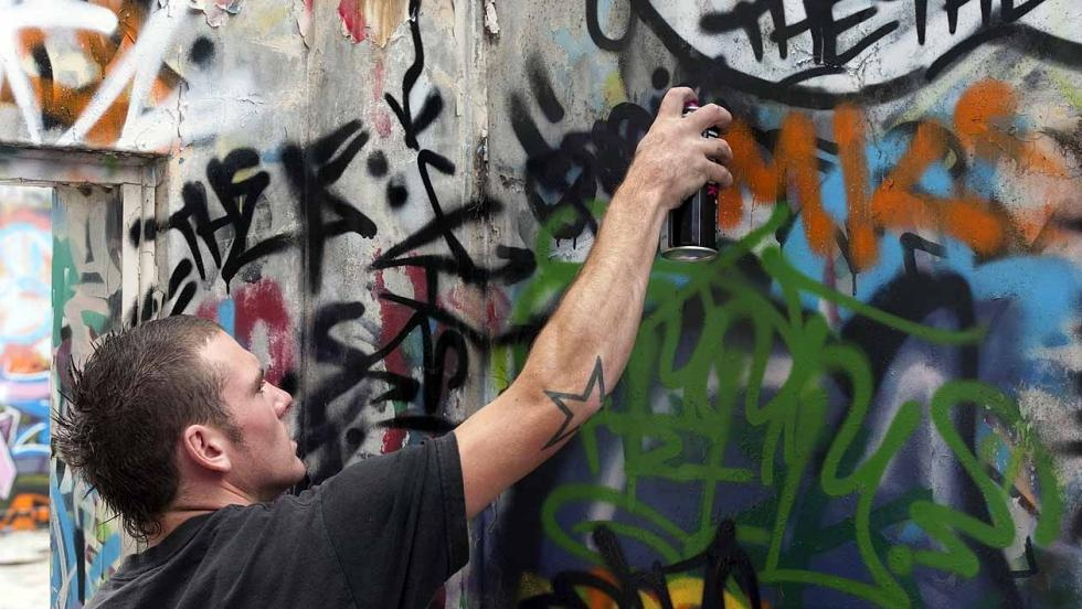 A Young Man sprays graffiti onto a wall
