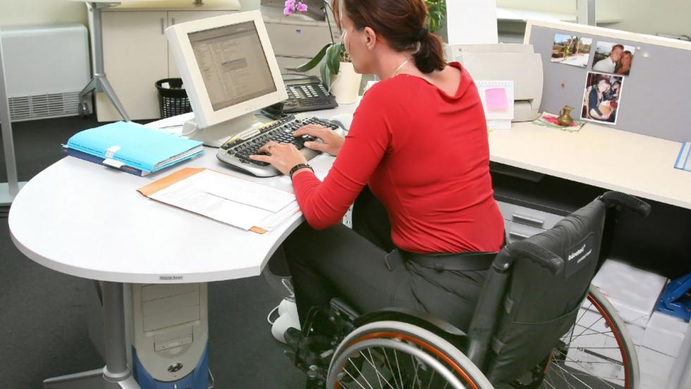 A woman in a wheelchair sits at an office desk