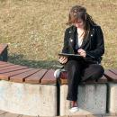 Young woman using her tablet alone in a public place