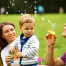 A young man and a young woman blow bubbles for a 1 year old child.