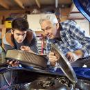 A young man and an older man work under the bonnet of a car
