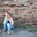 Young woman sat in front of a crumbling brick wall
