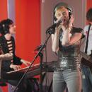 A young woman sings at a microphone with other other people playing instruments